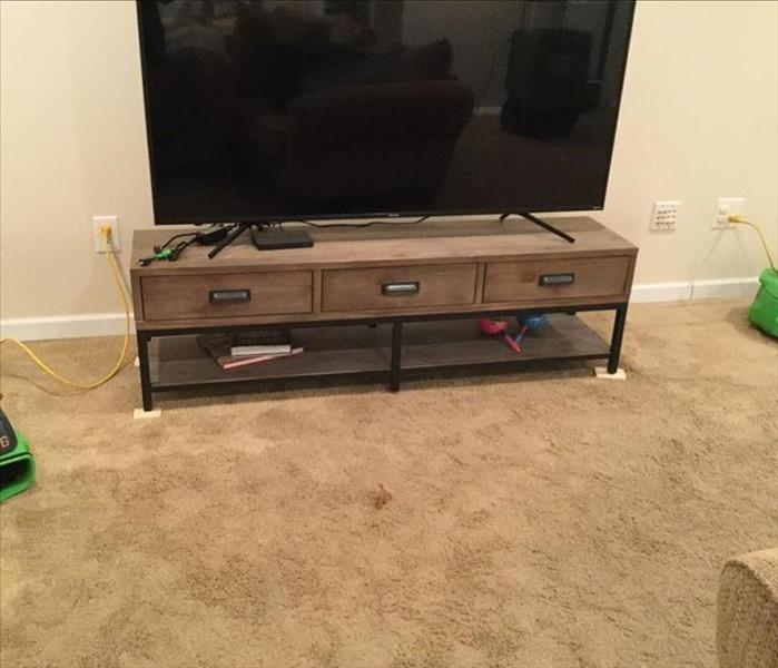 TV stand by carpeted walkway wet but not soggy from water