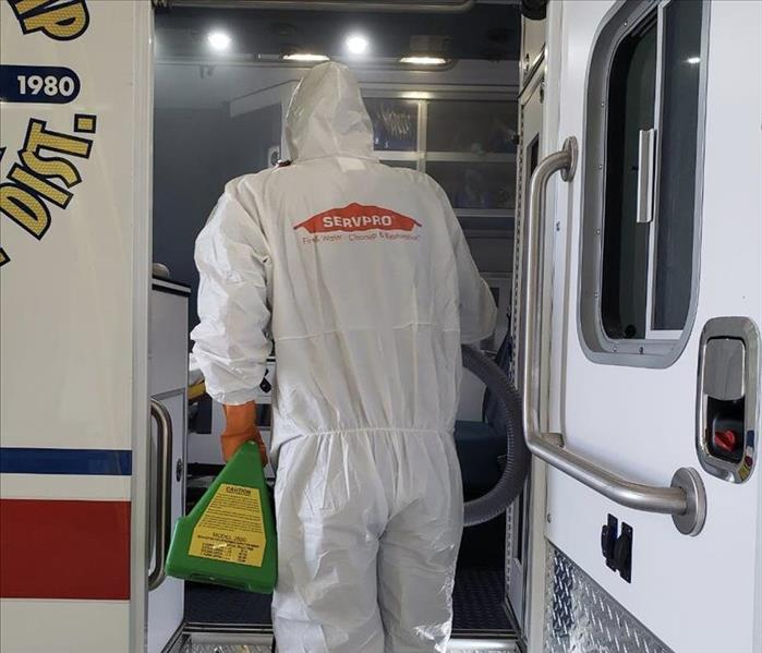 worker in white Tyvek suit with SERVPRO logo on the back entering an emergency vehicle