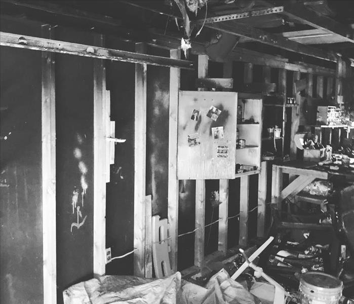 black and white image of an interior room devastated by fire, charred wood, framing, contents covered in soot