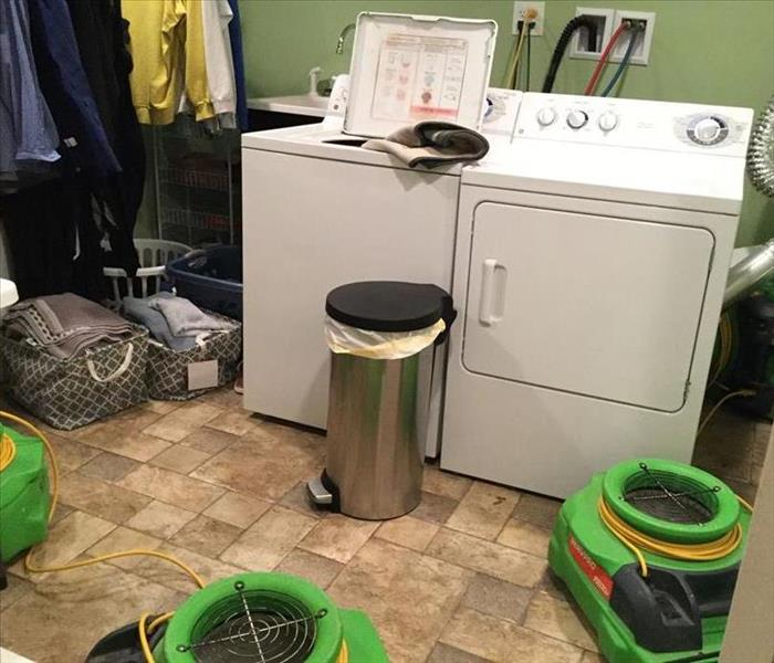 washer and dryer in laundry room on tile floor with green SERVPRO air movers on floor. trash can in front of washer